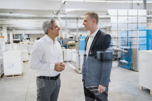 Two businessmen talking in a factory - DIGF09162