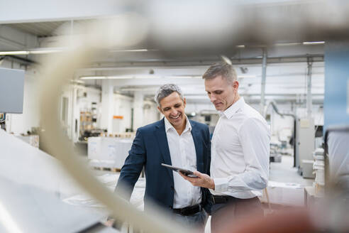 Two smiling businessmen looking at tablet in a factory - DIGF09171