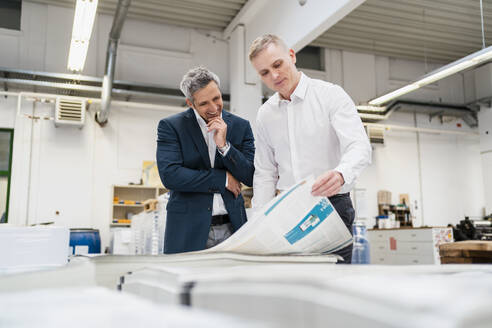 Two smiling businessmen discussing paper in a factory - DIGF09174