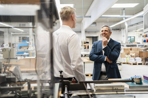 Two businessmen talking in a factory - DIGF09177