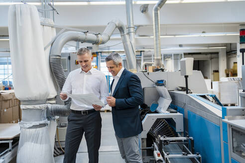 Two smiling businessmen discussing paper in a factory - DIGF09180