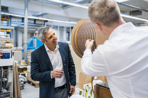 Two businessmen talking in a factory - DIGF09189