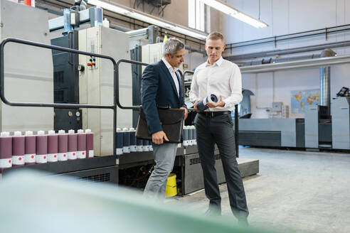 Two businessmen examining product in a factory - DIGF09195