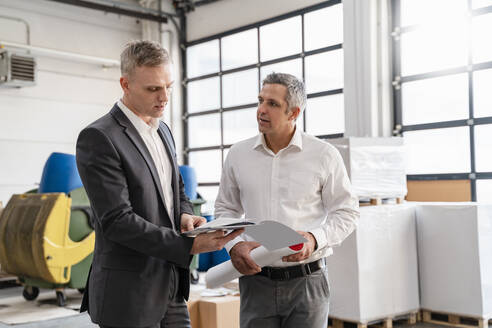 Two businessmen talking in a factory - DIGF09267
