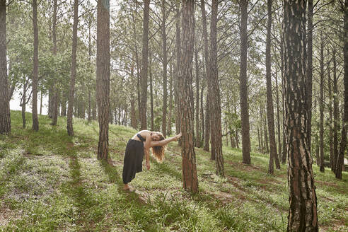 Barefoot young woman doing stretching exercise in the woods - VEGF01307