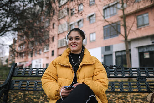 Portrait of happy young woman sitting on bench in autumn listening music with headphones and smartphone - GRCF00015