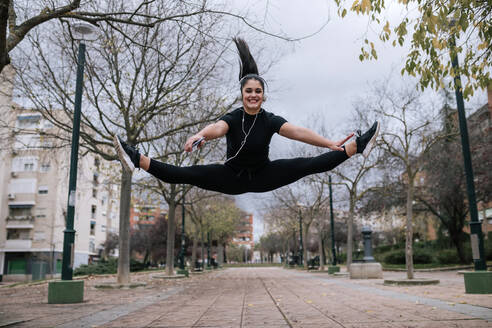 Portrait of young woman in black sportswear jumping in the air while listening music with headphones - GRCF00018