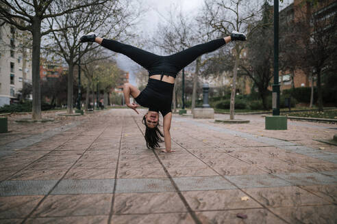 Young woman in black sportswear doing handstand on one hand - GRCF00021