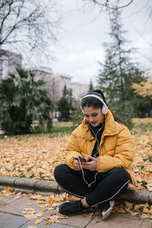 Young woman listening music with headphones and smartphone in autumn - GRCF00024