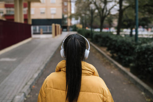 Back view of woman with black hair listening music with headphones on the street - GRCF00027