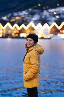 Woman wearing a yellow jacket and sitting at harbour in Bergen, Norway - DGOF00007