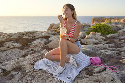 Young woman sitting on rocky beach, eating candies - EPF00645