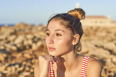 Portrait of a young woman on a rocky beach - EPF00666