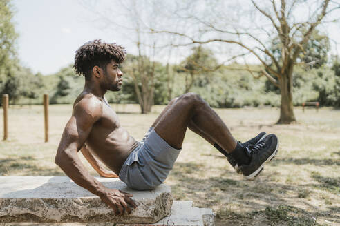 Young man lifting legs during workout on stone bench in park - FBAF01197