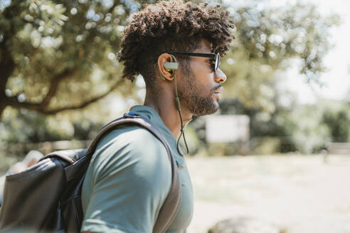 Young man with earphones in a park - FBAF01203