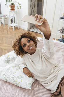 Happy young woman lying in bed taking a selfie - VPIF01924