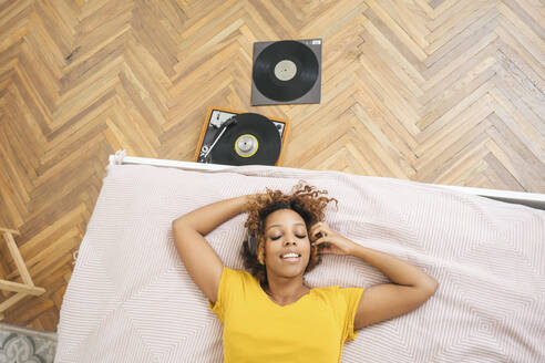 Young woman lying on bed listening to music with headphones and record player - VPIF01933
