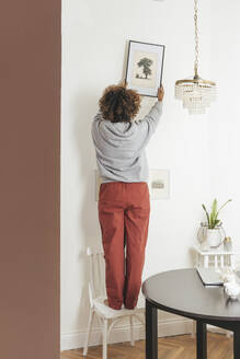 Young woman hanging up picture at home - VPIF01975