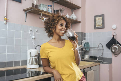 Smiling young woman drinking glass of red wine in kitchen - VPIF01984