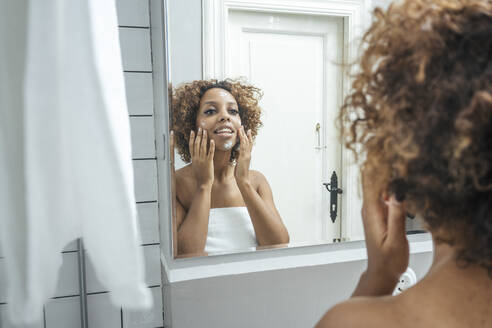 Young woman in bathroom applying face cream - VPIF01996
