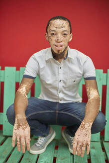 Young man with vitiligo on a green bench in front of a red wall - VEGF01358