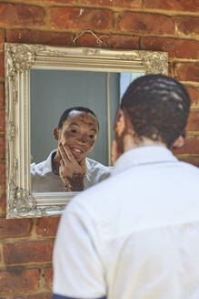 Young man with vitiligo looking in the mirror - VEGF01367