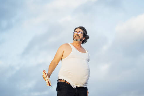 Man with beer belly holding sandwich - OCMF00988