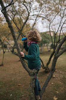 Boy in autumn watching something with binoculars - GRCF00036