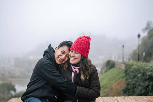 Young Mexican couple hugging on a cloudy day - GRCF00050