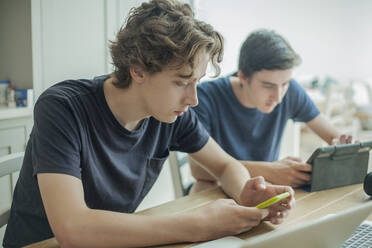 Two teenage boys using smartphone and tablet on table at home - AJOF00086