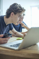 Foused teenage boy using laptop and smartphone on table at home - AJOF00089