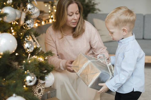 Mother giving present to her little son near Christmas tree - EYAF00799