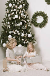 Two little girls sitting in front of Christmas tree opening Christmas presents - EYAF00802