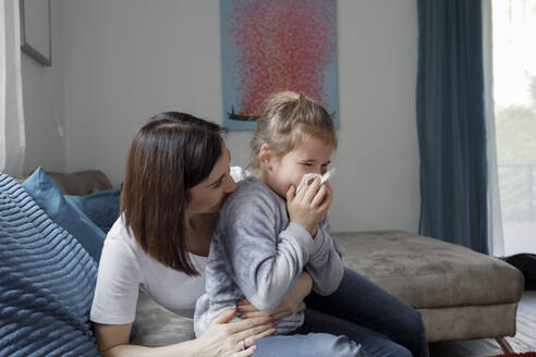 Mother sitting with daughter blowing her nose on couch in living room at home - KMKF01158
