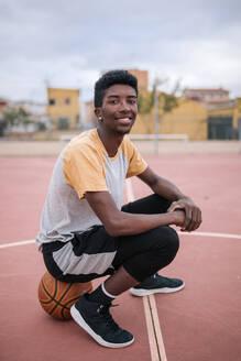 Teenager sitting on basketball - GRCF00058