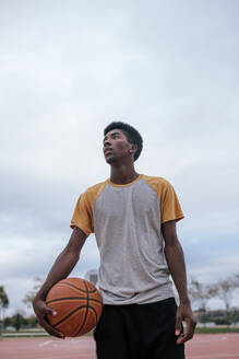 Teenager holding basketball with his arm - GRCF00070