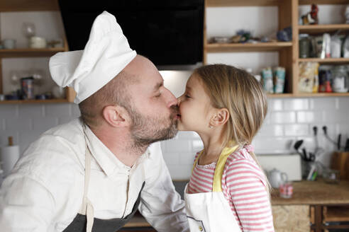 Father and daughter cooking in the kitchen - KMKF01169
