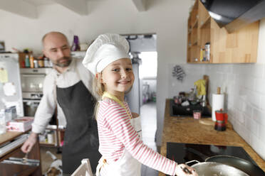 Father and daughter cooking in the kitchen - KMKF01172
