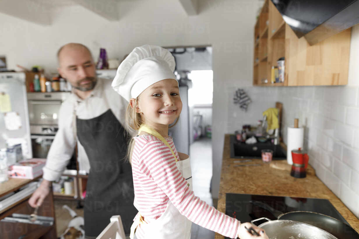 Father And Daughter Cooking In The Kitchen Stockphoto
