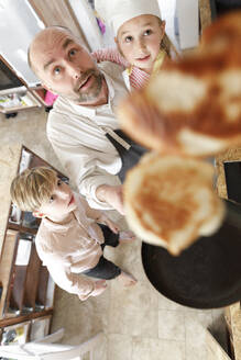 Father and daughter cooking in the kitchen, turning pancakes in the air - KMKF01175