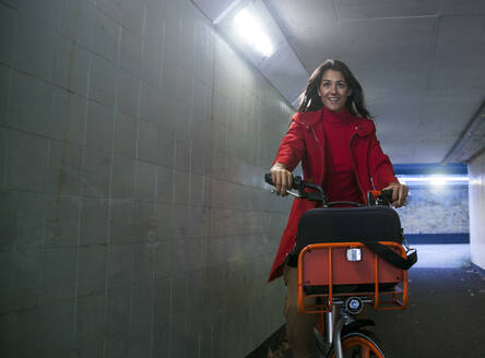 Young woman riding through an underpass on a rental bike - AJOF00094