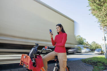 Young woman sitting on rental bike, using smartphone - AJOF00106
