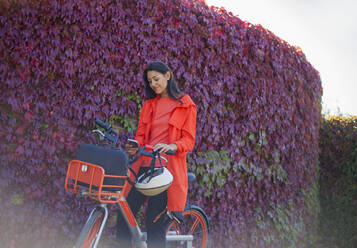 Young woman activating rental bike with smartphone app - AJOF00109