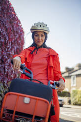 Young woman riding bicycle, wearing saftey helmet - AJOF00112