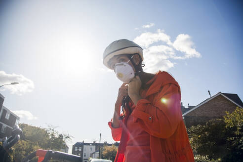 Woman wearing face mask, adjusting her cycle helmet m - AJOF00115