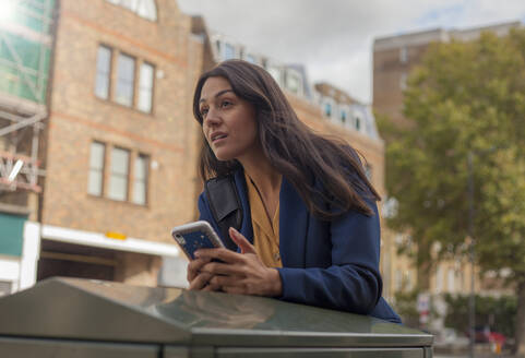 Portrait of woman, using smartphone in the city - AJOF00121