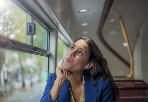 Young woman listening music on a bus with earphones - AJOF00124