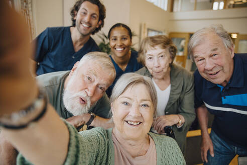 Retired elderly woman taking selfie with friends and caregivers at retirement home - MASF16204