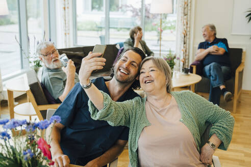Smiling senior woman taking selfie with male nurse while sitting at retirement home - MASF16228