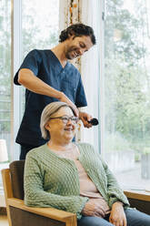 Smiling male nurse brushing senior woman's hair at retirement home - MASF16264